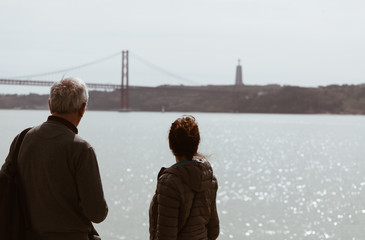 Senior Man and young girl looking the bridge in Lisbon - Portugal - travel family concept .