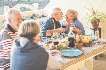 Senior couple having fun at barbecue dinner in home terrace