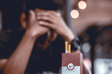 Man in T-shirt are stressed because they want to quit smoking. Focus at Cigarettes Box. Shallow depth of field.