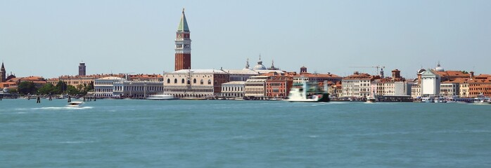 island of venice with ancient palaces and bell towers with long exposure time and the wake of the movement of ships