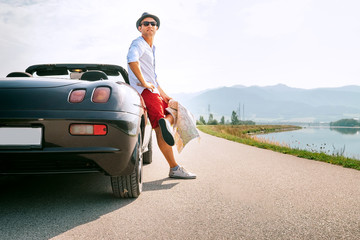 Man traveler on cabriolet car rest on picturesque mountain road
