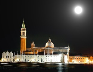 Church of Saint Geroge in Venice by night and the bright trails left by the passing ships with moon