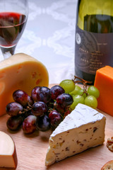 Still life red wine, roquefort cheese, red and green grapes on wooden plate