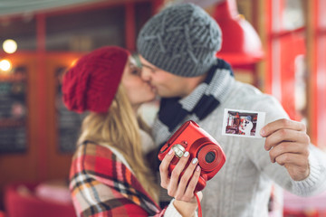 Kissing couple with a red polaroid