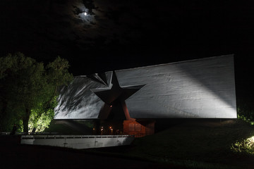 Main entrance to Brest fortress with carved five-pointed star at night - view to hero soldier monument, Belarus. Brest fort first point attacked by Germans in USSR. Brest, Belarus