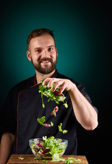 Portrait of a handsome male chef cook making tasty salad on a blurred aquamarine background