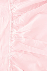 Texture of fabric is pink color background,Creased pink cloth material fragment as a background