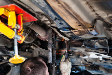 repairer welds silencer on car by argon welding