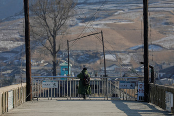 A man looks towards North Korea from the Broken Bridge over the Yalu River north of the towns of Sinuiju in North Korea and Dandong in China
