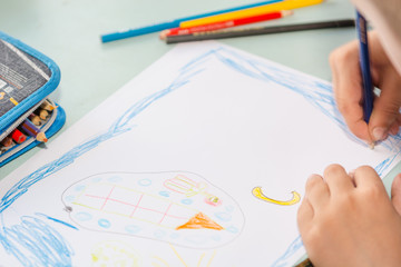 The child is drawing. Draws on a piece of paper. Children have fun. Draws a postcard. The child draws with a pencil.