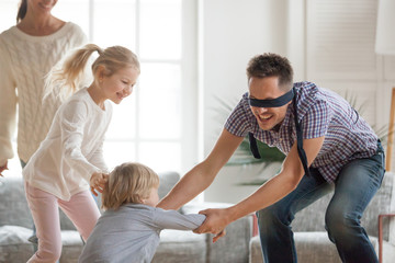 Happy young family of four playing hide and seek game at home, blindfolded father trying to catch children escaping, parents and kids having fun laughing spending free time together in living room