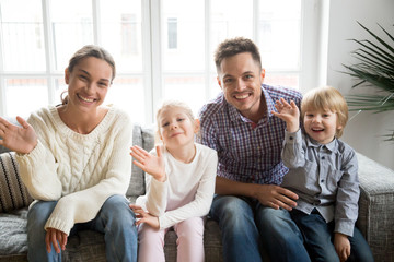 Portrait of happy multi-ethnic family with adopted kids waving hand looking at camera, smiling couple with children sitting on sofa making video call, greeting online by webcam, recording videoblog