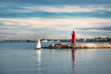 Small sailing boat falls in the port of Trani in Puglia at sunset