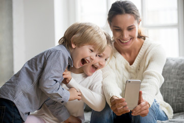 Smiling mother taking selfie with cute kids on smartphone, happy young mom laughing making photo with little son and daughter at home, single mommy and adopted children playing having fun with phone