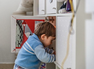 A little boy looks for his toys inside a closet