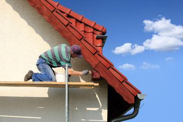 Mężczyzna, malarz maluje farbą okap czerwoego dachu.