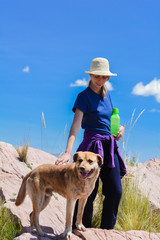 Poster Camping Young caucasian woman with her dog enjoing the nature.