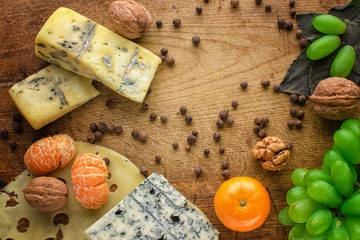Grapes, cheeses, honey and nuts over rustic weathered wood. Top view.