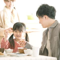 父親と箸の持ち方の練習をする女の子