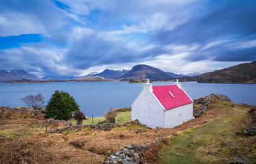 The famous red roof cottage on the shore of Loch Shieldaig, near Torridon on the west coast of Scotland. On the route of the North Coast 500 road trip.