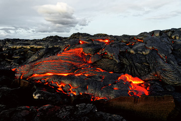 A lava flow emerges from an earth column and flows in a black volcanic landscape, in the sky shows the first daylight - Location: Hawaii, Big Island, volcano
