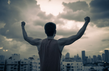 Strong man in the city with fist in the air. People overcoming fear, determination, and power concept.