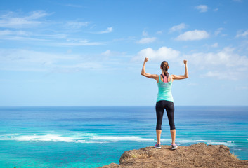 Strong woman flexing outdoors. Female power, strength, and self motivation concept.