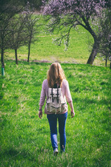 Woman traveler walking in blossoming orchard at springtime