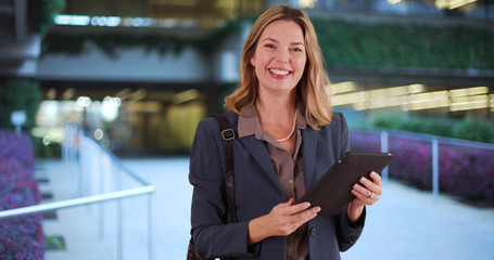 Middle aged adult business woman using tablet device outside building