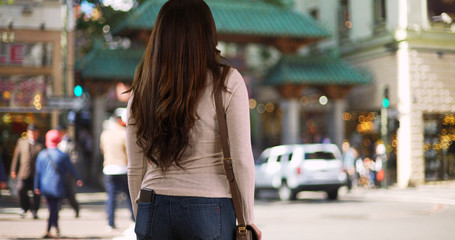 Latina female standing on street in shopping district looking around frustrated