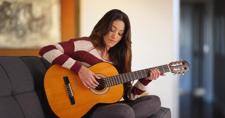 Inspired young Latina woman composing song on acoustic guitar at home