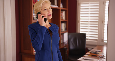 Mid shot of successful self-employed female making phone call inside home office