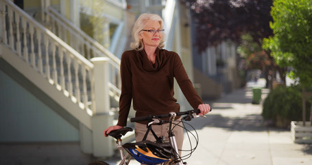 Joyful mature Caucasian woman resting from bike ride on sunny day in residential area