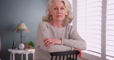 Somber woman in her 50s sitting on chair inside home posing with seriousness
