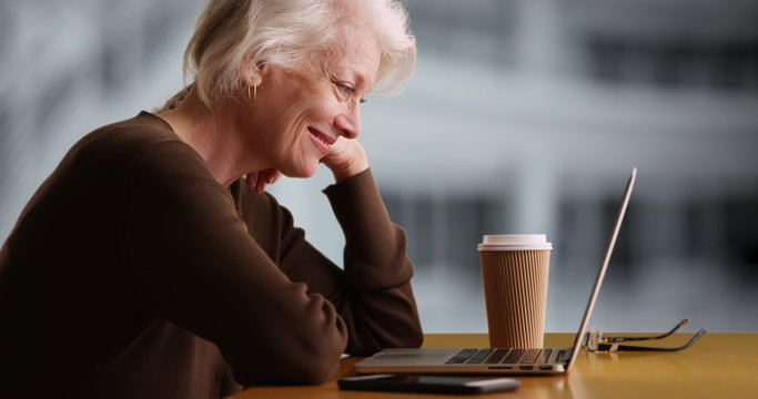 Side profile of mature white lady watching funny video online outside office building