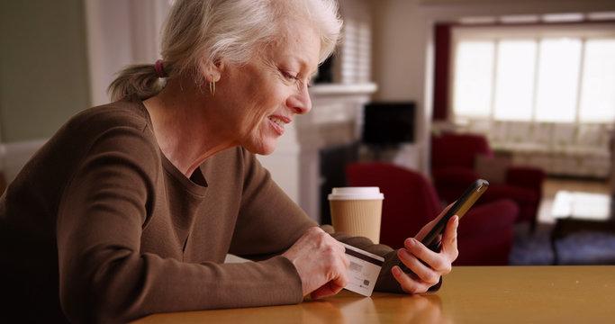 Modern senior woman shopping online through her phone sitting inside home