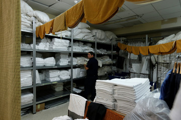 A worker stacks bed linen in the laundry room at the Radisson Blu Resort and Spa Golden Sands at Golden Bay outside Mellieha