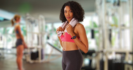 Beautiful African woman at gym with towel around neck posing proudly