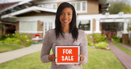 Portrait of cheerful black woman advertising home for sale