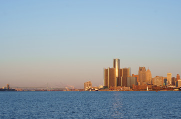Downtown Detroit view from Belle-Isle during sunrise with view on Bridge to Windsor, Ontario, Canada. The morning sun reflect on GM towers.