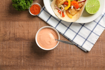 Tasty creamy sauce for fish taco in bowl on wooden table