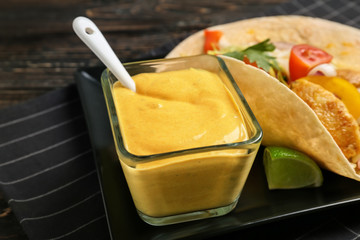 Plate with tasty creamy sauce in bowl and fish taco on table