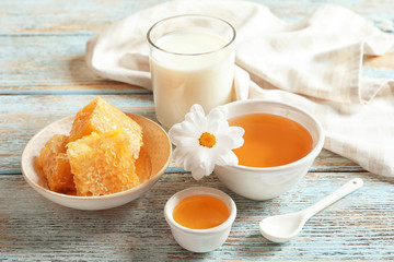 Beautiful composition with milk and honey on wooden background
