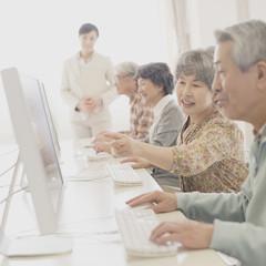 パソコン教室で講習を受けるシニア