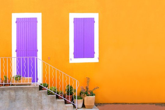 Vibrant yellow house front with purple shuttered door and window, Provence, France. Copy space.