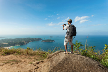 travel man with backpack standing take a photo with smartphone and see beautiful scenery landscape nature view on rock mountain in phuket thailand.