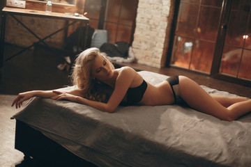 Sexy girl in lingerie on bed in the evening.