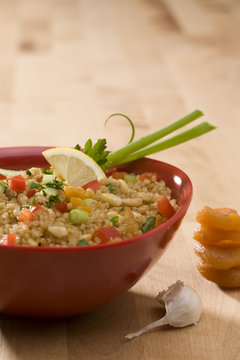 quinoa salad with vegetables in red bowl