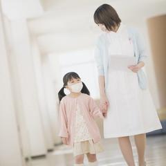 女の子の手をひく看護師