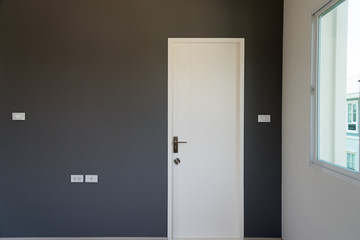 Gray wall decoration with white door closed.